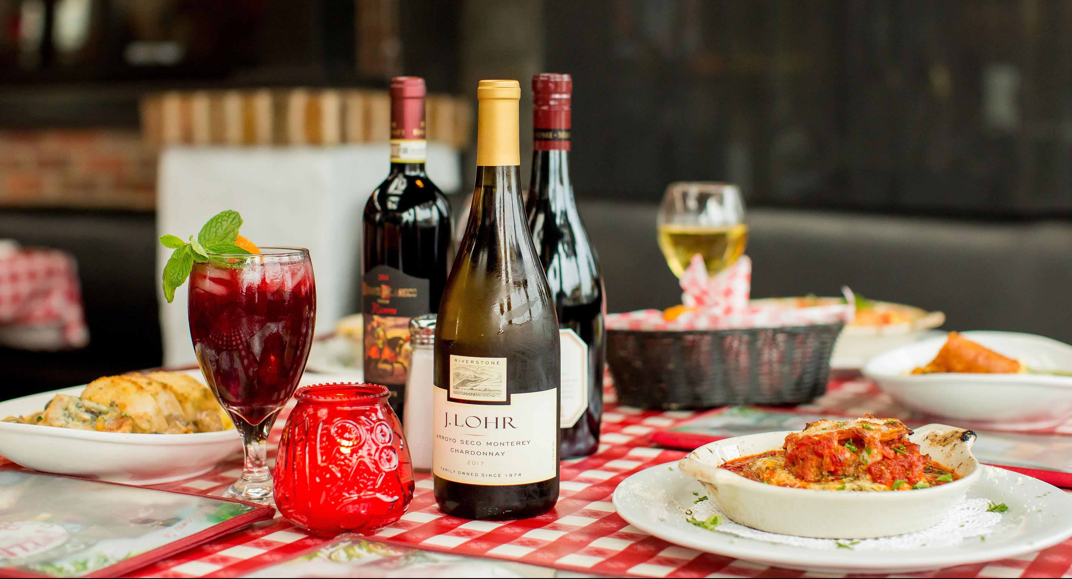 Bottles of wine and italian cuisine on red and white checkered tablecloth.